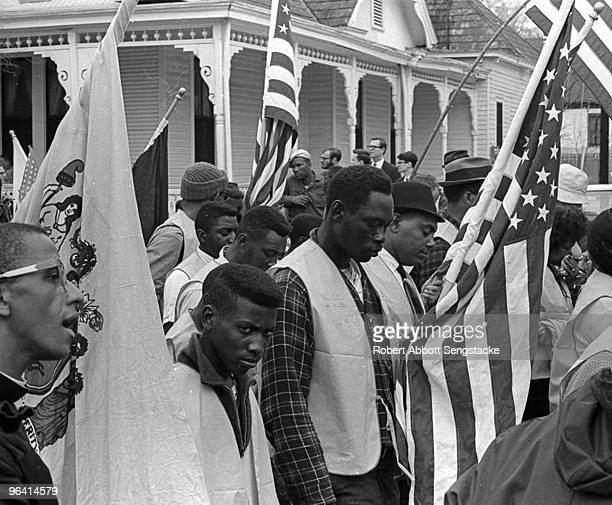 Marchers carrying state and American flags pause for a moment of silence during the Selma to Montgomery march held in support of voter rights Alabama...