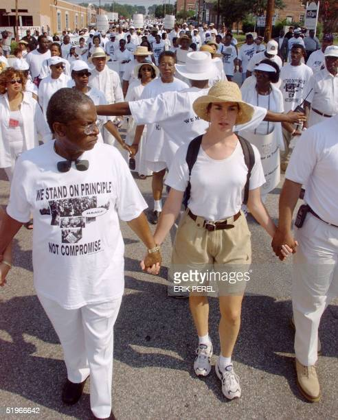 NAACP marchers dressed in white as a show of unity conduct a silent march 01 July 2000 to the Capitol in Columbia SC to protest the placement of the...