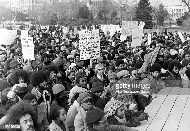 Marchers gather in front of the white house in Washington DC to hear Jesse Jackson Sr speak at an event honoring Martin Luther King Jr January 25 1975