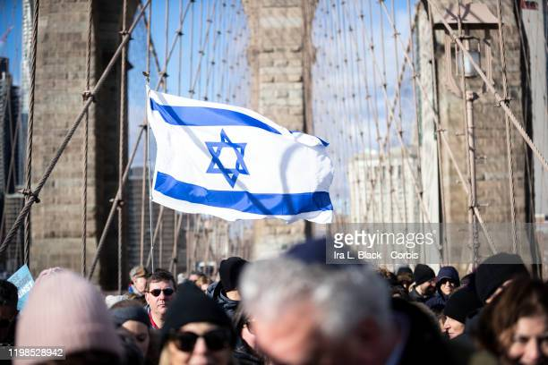 Marchers hold an Israeli flag as they walk across the Brooklyn Bridge with the arch behind them. This was part of the effort to support the No Hate...