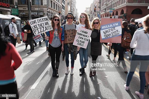 Marchers hold signs during the Women's March on January 21 2017 in Los Angeles California Tens of thousands of people took to the streets of Downtown...