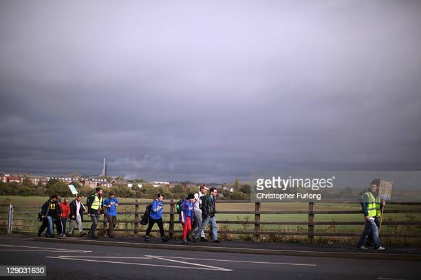 Marchers make their way through the South Yorkshire village of Royston as they reenact the Jarrow Crusade for employment on October 11 2011 in...