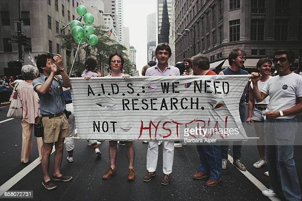 Marchers on a Gay Pride parade through Manhattan, New York City, carry a banner which reads 'A.I.D.S.: We need research, not hysteria!', June 1983.