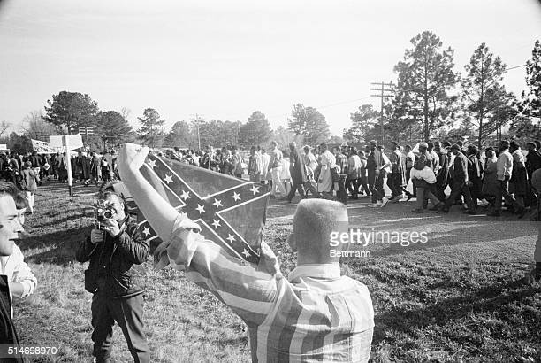 Marchers participating in the Selma to Montgomery civil rights march walk past a white youth holding a confederate flag