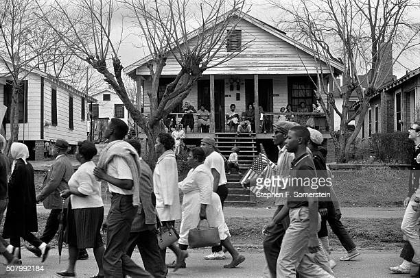 Marchers pass by a house with people on the porch on route 80 Jefferson Davis Highway during the Selma to Montgomery civil rights march on March 25...