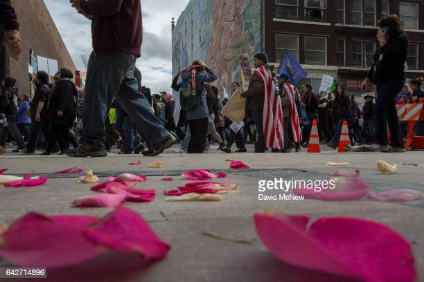Marchers pass rose pedals outside a wedding chapel during the Immigrants Make America Great March to protest actions being taken by the Trump...
