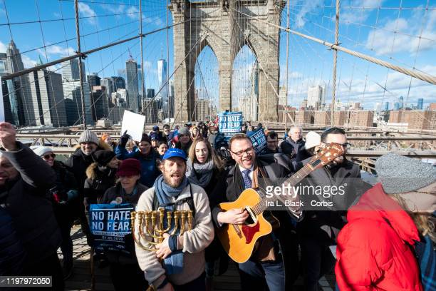 """Marchers playing guitar and holding a Menorah walking across the Brooklyn Bridge while other carry signs that says """"No Hate No Fear"""" with the..."""