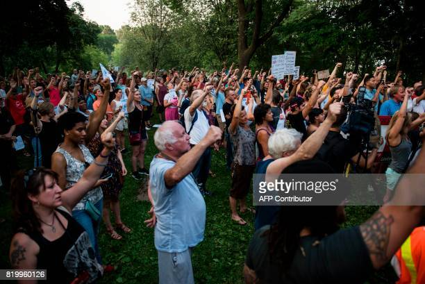 Marchers raise their fists at Beard's Plaisance Park on July 20 2017 in Minneapolis Minnesota Several days of demonstrations have occurred after the...