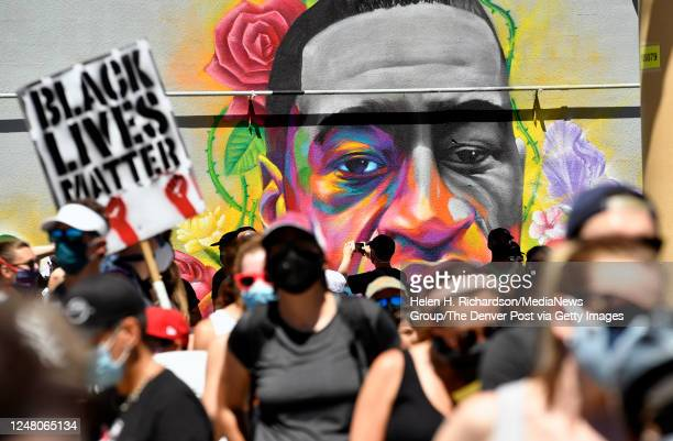 Marchers walk by a mural of George Floyd painted on a wall along Colfax Avenue on June 7, 2020 in Denver, Colorado. George Floyd was killed in the...