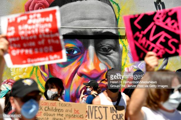 Marchers walk by a mural of George Floyd painted on a wall along Colfax Avenue on June 7 2020 in Denver Colorado George Floyd was killed in the hands...