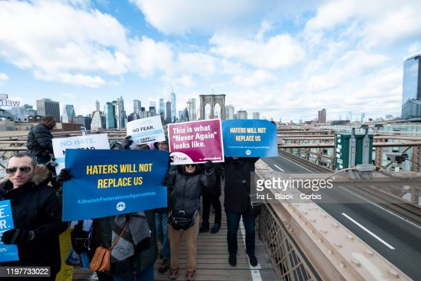 """Marchers walking across the Brooklyn Bridge carrying a sign of """"Haters Will Not Replace Us"""" and """"No Fear"""" with the Freedom Tower behind them. This..."""