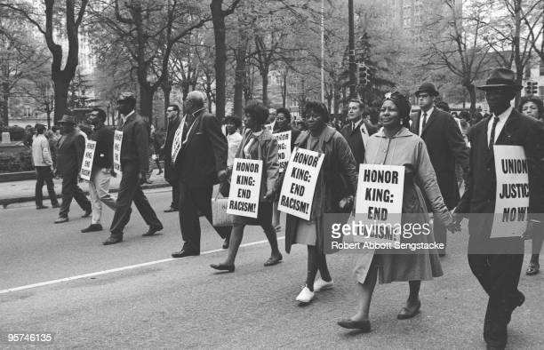 Marchers wear signs that read 'Honor King End Racism' and 'Union Justice Now' as they participate in the Sanitation Workers march soon after the...