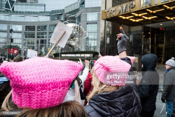 Marchers wearing pink hats hold up a middle finger as they walk in front of Trump International Tower during the Woman's March in the borough of...