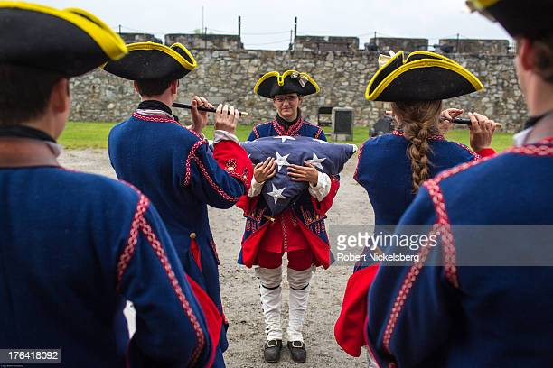 A marching band at Fort Ticonderoga dressed as French soldiers from 1755 plays a striking the colors tune for lowering the flag August 1 2013 in...