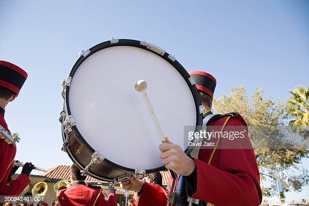 Marching band drummer holding bass drum