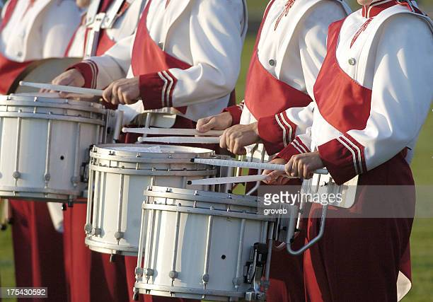 Marching band playing drums with red uniform