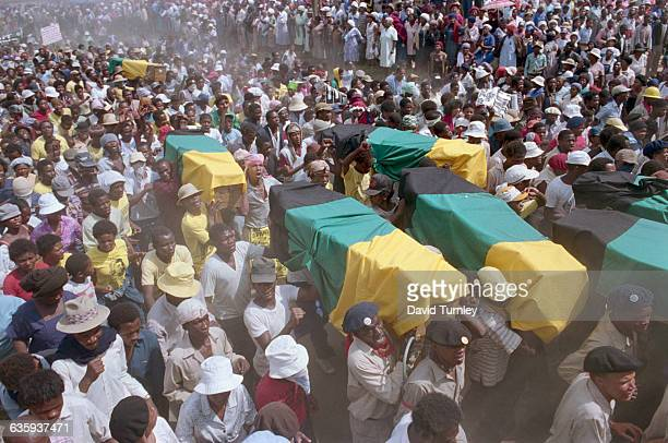 Marching demonstrators carry the victims of local violence to the cemetery