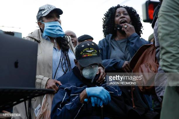 Marcia CarterPatterson and stepdaughter Christy Cloy chant during a vigil at the intersection where CarterPatterson's son Manuel Ellis a 33yearold...