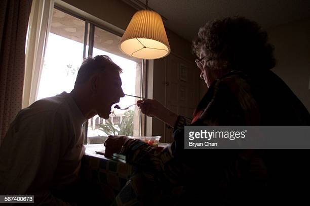 Marcia Flannery feeds her son Page Dye who is develomentally disabled in their Costa Mesa hotel room She and husband Mike Flannery picked up Page...