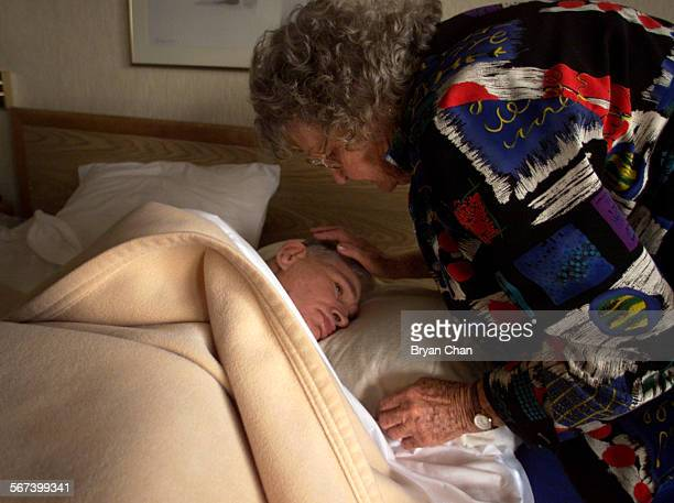 Marcia Flannery tucks her son Page Dye who is develomentally disabled into bed for a nap in their Costa Mesa hotel room She and husband Mike Flannery...