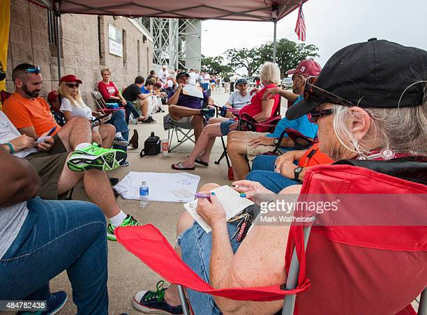 Marcia Grace right of Mobile AL works a puzzle book outside LaddPeebles Stadium in Mobile as she waits prior to a Donald Trump campaign rally outside...