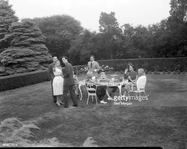 Marcia Meehan with group of friends at Mr and Mrs Joseph Meehan's cocktail party, Souhampton, NY, July 10, 1960