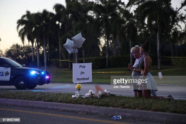 Marcia Miller and Rae Ricketts pray for the victims near a checkpoint setup at Marjory Stoneman Douglas High School where 17 people were killed on...