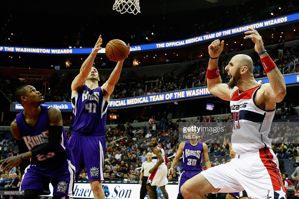 Marcin Gortat #13 of the Washington Wizards reacts to a call as Ben McLemore #23 and Kosta Koufos #41 of the Sacramento Kings go for the ball late in the fourth quarter of the Wizards 113-99 win at Verizon Center on December 21, 2015 in Washington, DC.