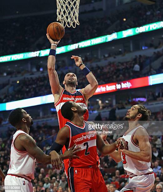 Marcin Gortat of the Washington Wizards shoots over teammate John Wall and Aaron Brooks and Joakim Noah of the Chicago Bulls at the United Center on...