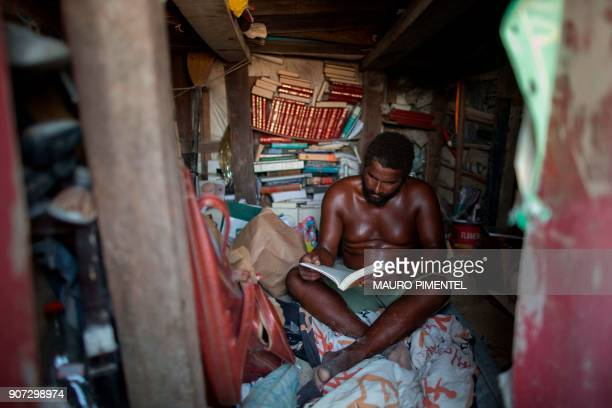 Marcio Mizael Matolias reads a book inside his sand castle where he lives on the beach of Barra da Tijuca in Rio de Janeiro Brazil on January 18 2018...