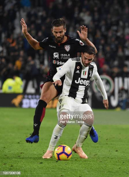 Marco Andreolli of Cagliari competes for the ball with Mattia De Sciglio of Juventus during the Serie A match between Juventus and Cagliari on...