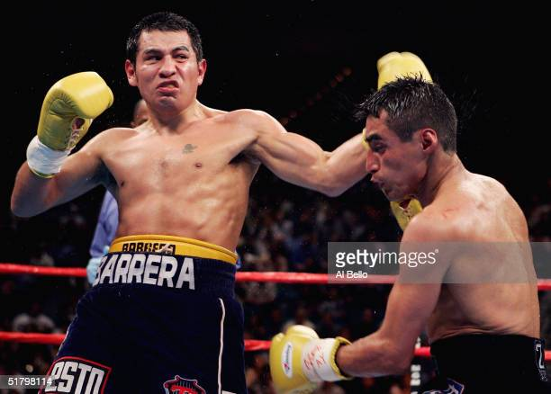 Marco Antonio Barrera lands a left handed hook to the head of Erik Morales during a fight for the WBC World Super Featherweight Championship at the...