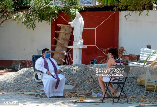 Marco Antonio Galeana parish priest of the Cordova church hears the confession of a devotee outside the church in Acapulco Mexico on April 9 2020...
