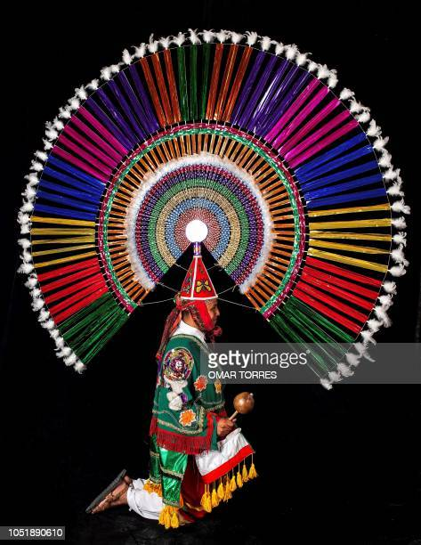 Marco Antonio Salas Suarez poses for a photograph with his 'Penacho' traditional costume during the presentation of the Huey Atlixcayotl Festival on...