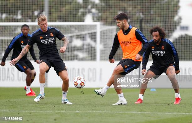 Marco Asensio and Toni Kroos of Real Madrid are training with teammates Marcelo Silva and David Alaba at Valdebebas training ground on October 16,...