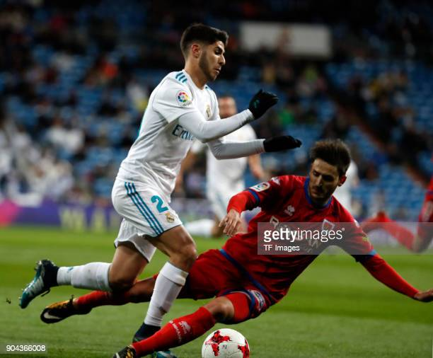 Marco Asensio of Real Madrid and a player of Numancia battle for the ball during the Spanish Copa del Rey match between Real Madrid and Numancia at...