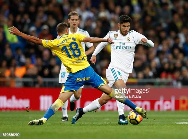 Marco Asensio of Real Madrid and Javi Castellano of Las Palmas compete for the ball during the La Liga match between Real Madrid and Las Palmas at...