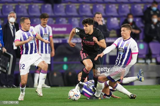 Marco Asensio of Real Madrid and Ruben Alcaraz of Valladolid compete for the ball during the La Liga Santander match between Real Valladolid CF and...