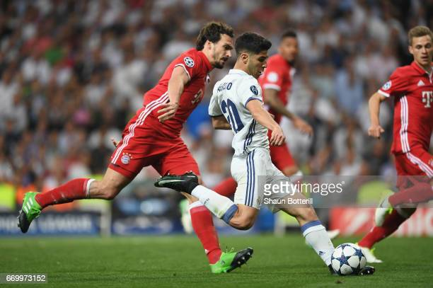 Marco Asensio of Real Madrid beats Mats Hummels of Bayern Muenchen to score their fourth goal during the UEFA Champions League Quarter Final second...