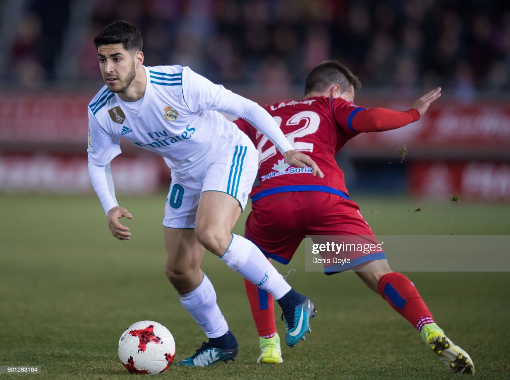 Marco Asensio of Real Madrid beats Pablo Larrea of Numancia during the Copa del Rey match between Numancia and Real Madrid at Nuevo Estadio Los Pajarito on January 4, 2018 in Soria, Spain.