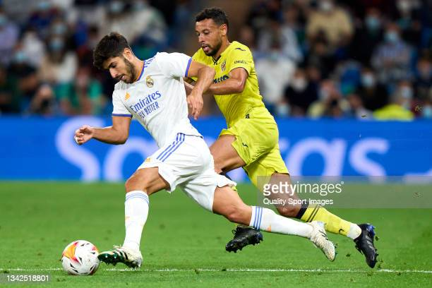 Marco Asensio of Real Madrid CF battle for the ball with Francis Coquelin of Villarreal CF during the La Liga Santander match between Real Madrid CF...