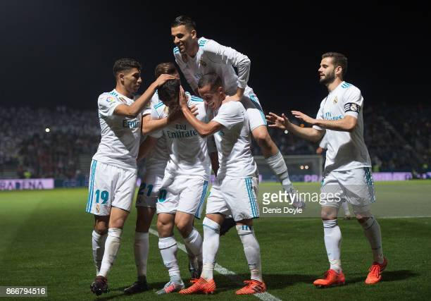 Marco Asensio of Real Madrid CF celebrates with teammates after scoring his team's opening goal from a penalty kick during the Copa del Rey Round of...