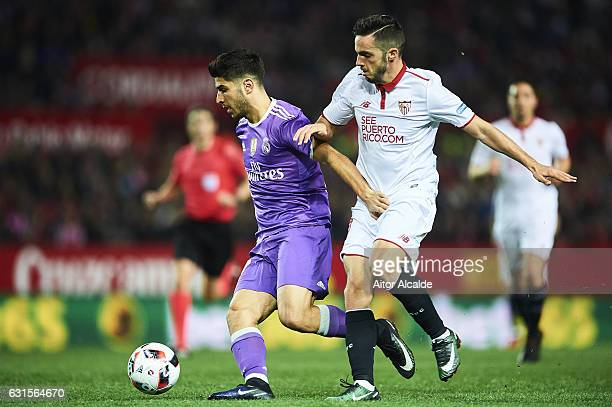Marco Asensio of Real Madrid CF competes for the ball with Pablo Sarabia of Sevilla FC during the Copa del Rey Round of 16 Second Leg match between...
