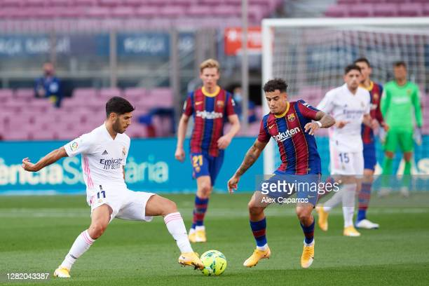 Marco Asensio of Real Madrid CF competes for the ball with Philippe Coutinho of FC Barcelona during the La Liga Santander match between FC Barcelona...