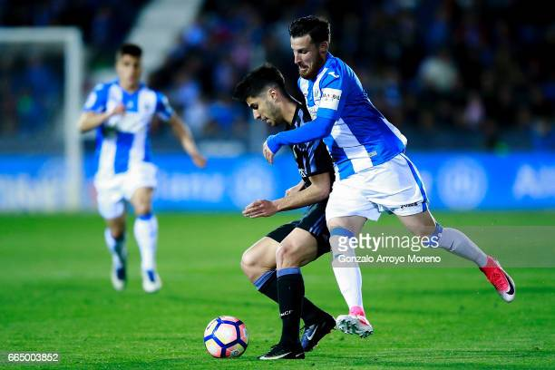 Marco Asensio of Real Madrid CF competes for the ball with Roberto Roman Triguero alias Tito of Deportivo Leganes during the La Liga match between CD...