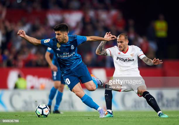 Marco Asensio of Real Madrid CF competes for the ball with Sandro Ramirez of Sevilla FC during the La Liga match between Sevilla FC and Real Madrid...