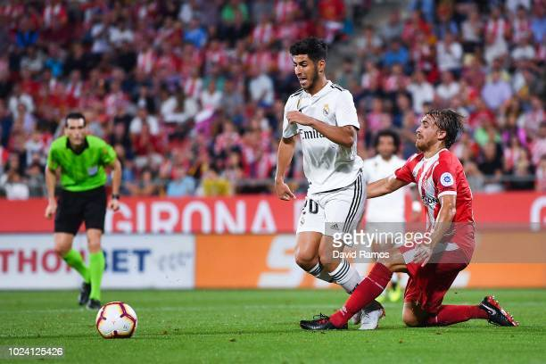 Marco Asensio of Real Madrid CF is brought down by Marc Muniesa of Girona FC during the La Liga match between Girona FC and Real Madrid CF at...