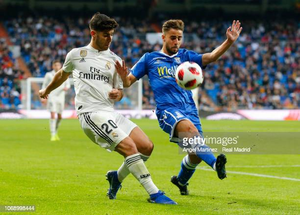 Marco Asensio of Real Madrid competes for the ball with Braim Amar Romero of Melilla during the Copa del Rey fourth round second leg match between...
