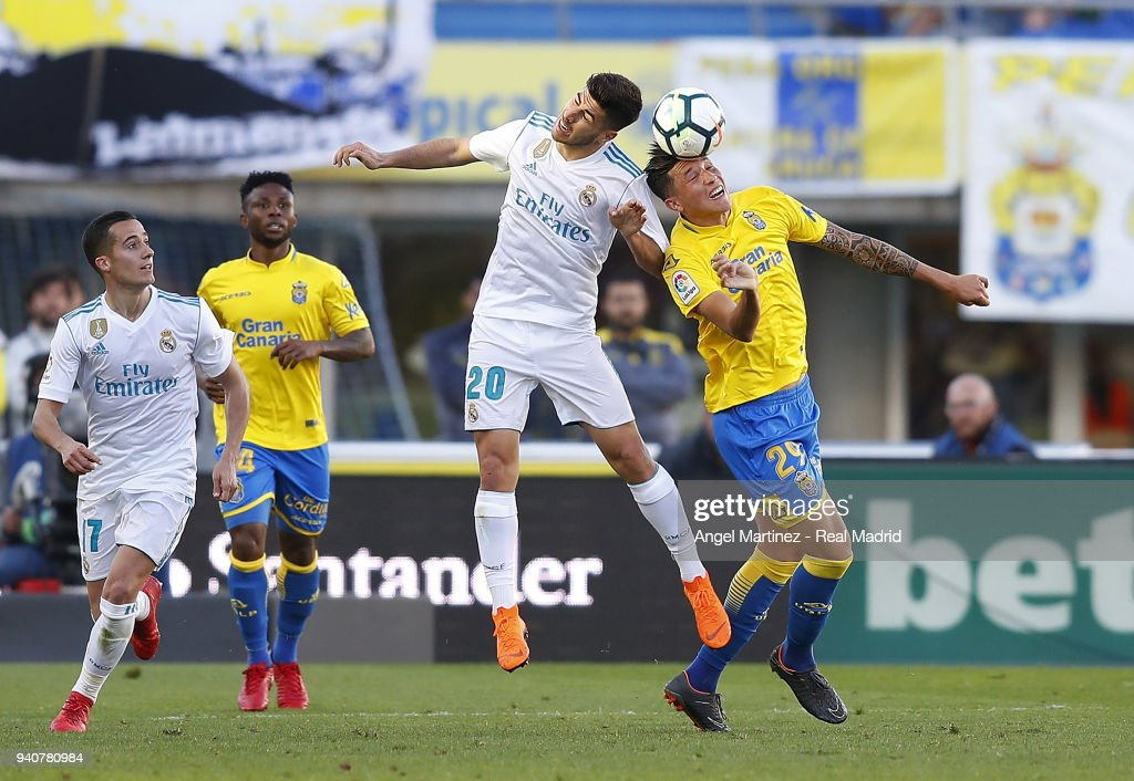 Marco Asensio of Real Madrid competes for the ball with Erik Exposito of UD Las Palmas during the La Liga match between UD Las Palmas and Real Madrid at the Gran Canaria stadium on March 31, 2018 in Las Palmas, Spain.