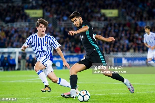 Marco Asensio of Real Madrid duels for the ball with Alvaro Odriozola of Real Sociedad during the La Liga match between Real Sociedad de Futbol and...